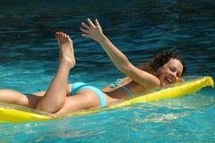 Jonge vrouw die op matras zwemt Royalty-vrije Stock Afbeeldingen