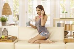 Jonge vrouw die op mobiel thuis spreken Royalty-vrije Stock Afbeeldingen