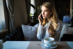 Jonge vrouw die op mobiele telefoon en het drinken koffie bij de lijst in koffie spreken stock afbeeldingen