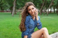 Jonge vrouw die op mobiele telefoon spreekt Royalty-vrije Stock Foto's