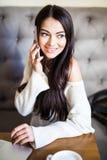 Jonge vrouw die op mobiele telefoon spreken en laptop in koffie met behulp van stock afbeeldingen