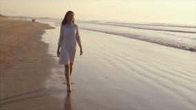 Jonge vrouw die op overzeese kust tijdens zonsondergang lopen stock video