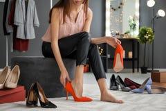Jonge vrouw die op schoenen probeert Stock Fotografie