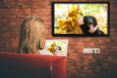 Jonge vrouw die op slimme TV letten Royalty-vrije Stock Afbeeldingen