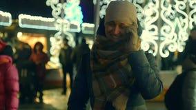 Jonge vrouw die op smartphone bij de markt van de Kerstmisstraat spreken stock footage