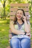 Jonge vrouw die op smartphone spreken en in het park op het bank Mooie wijfje lachen die op een parkbank ontspannen stock afbeelding