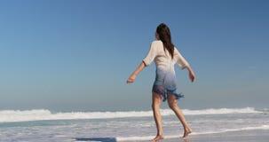Jonge vrouw die op strand in de zonneschijn 4k dansen stock footage