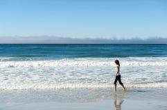 Jonge vrouw die op strand loopt stock afbeeldingen