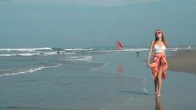 Jonge vrouw die op strand in Seminyak, Bali lopen stock videobeelden