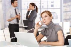 Jonge vrouw die op telefoon in bureau het glimlachen spreken royalty-vrije stock afbeelding