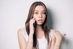 Jonge vrouw die op telefoon in bureau spreken stock afbeeldingen