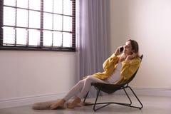 Jonge vrouw die op telefoon dichtbij venster met zonneblinden thuis spreekt royalty-vrije stock fotografie