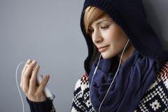 Jonge vrouw die op telefoon spreken die earbuds gebruiken Royalty-vrije Stock Afbeelding