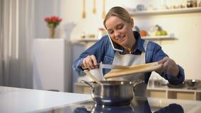 Jonge vrouw die op telefoon spreken en tomatensaus, gemakkelijk voedselrecept voorbereiden stock videobeelden
