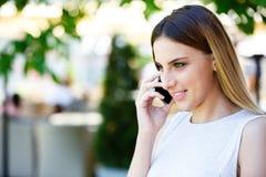 Jonge vrouw die op telefoon spreken terwijl status dichtbij koffie` s tuin stock afbeeldingen