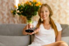 Jonge vrouw die op TV in de woonkamer letten Royalty-vrije Stock Afbeeldingen