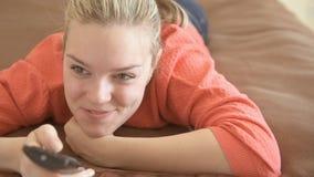 Jonge vrouw die op TV en het glimlachen letten stock videobeelden