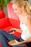 Jonge vrouw die op TV let Royalty-vrije Stock Foto
