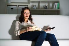 Jonge vrouw die op TV letten royalty-vrije stock afbeeldingen