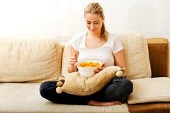 Jonge vrouw die op TV letten en spaanders eten Royalty-vrije Stock Foto's