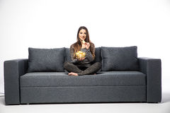 Jonge vrouw die op TV letten en spaanders eten die op bank zitten Stock Foto