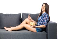 Jonge vrouw die op TV letten en spaanders op witte achtergrond eten Stock Fotografie