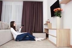 Jonge vrouw die op TV op bank in woonkamer letten die afstandsbediening met behulp van stock afbeelding