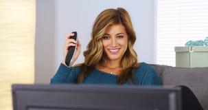 Jonge vrouw die op TV op laag let Royalty-vrije Stock Foto