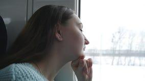 Jonge vrouw die op venster tijdens het berijden op trein kijken Profiel die van aantrekkelijk meisje op spoorweg reizen Langzame  stock videobeelden