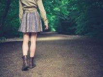 Jonge vrouw die op weg in bos lopen Royalty-vrije Stock Afbeeldingen