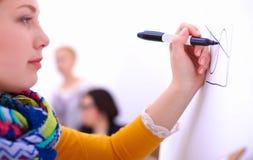 Jonge vrouw die op whiteboard met witte copyspace trekken Stock Foto