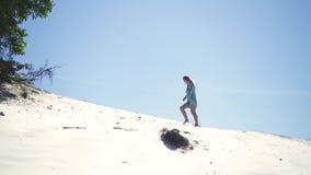 Jonge vrouw die op zandig duin in hete woestijn op blauwe hemelachtergrond lopen Mooi meisje die op zandige heuvel lopen terwijl stock video