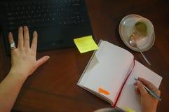 Jonge vrouw die op zijn bureau op een boek achter een gouden kop schrijven stock afbeelding