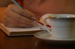 Jonge vrouw die op zijn bureau op een boek achter een kop schrijven royalty-vrije stock afbeeldingen