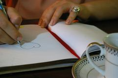 Jonge vrouw die op zijn bureau een haard trekken achter een kop stock foto