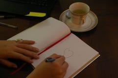 Jonge vrouw die op zijn bureau een haard trekken op een boek stock afbeeldingen