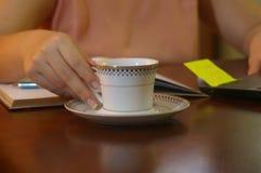 Jonge vrouw die op zijn bureau een kop met een lepel houden royalty-vrije stock foto