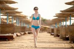 Jonge vrouw die op zonnig zandstrand lopen Stock Afbeelding