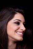 Jonge vrouw die, op zwarte achtergrond glimlacht stock afbeelding