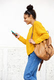 Jonge vrouw die in openlucht en mobiele telefoon lopen met behulp van royalty-vrije stock foto