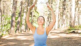 Jonge vrouw die in openlucht in het park van de de lentezomer mediteren royalty-vrije stock afbeeldingen