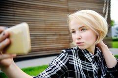 Jonge vrouw die in openlucht selfie maken Stock Foto