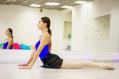 Jonge vrouw die opwarming op de Mat in de gymnastiek doen stock fotografie