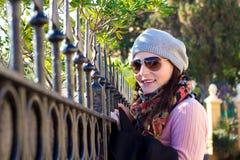Jonge Vrouw die over een Omheining en het Glimlachen kijkt Stock Afbeelding