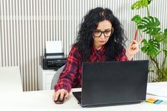 Jonge vrouw die over nieuw opstarten in modern bureau werken businessplan, nieuwe strategie Vrouwenzitting op haar werkende plaat royalty-vrije stock afbeeldingen