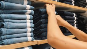 Jonge vrouw die paar blauwe denimjeans nemen van stapels in kledingswinkel Vrouwelijke handen die correcte broekgrootte in het wi stock footage