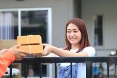 Jonge vrouw die pakket van de leveringsmens ontvangen die wat pac brengen royalty-vrije stock foto