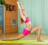 Jonge vrouw die pilates binnen hebben Stock Foto