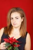 Jonge vrouw die Poinsettia houdt Stock Afbeeldingen