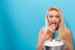 Jonge vrouw die popcorn eten Royalty-vrije Stock Afbeeldingen